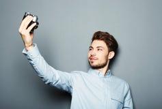 Stilig hållande kamera för ung man och danandeselfie royaltyfri foto