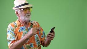 Stilig hög skäggig turist- man som är klar för semester mot grön bakgrund arkivfilmer
