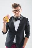 Stilig hipster för Dj som äter på munken från hans kopp Royaltyfria Bilder
