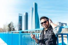 Stilig Hipster Guy Listening Music på hörlurar och användamobiltelefonen arkivbilder
