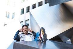 Stilig Hipster Guy Listening Music på hörlurar och att le arkivbild