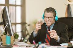 Stilig idérik affärsman som lyssnar till hörlurar och är enfaldig arkivfoton