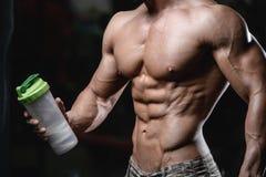 Stilig idrotts- konditionman som rymmer en shaker och poserar idrottshall arkivfoto