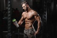 Stilig idrotts- konditionman som rymmer en shaker och poserar idrottshall Royaltyfria Bilder