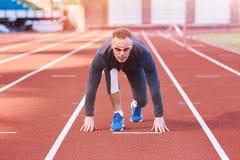 Stilig idrotts- man i början av stadiontrampkvarnen royaltyfri bild