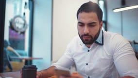 Stilig idrotts- man som har en kopp kaffe, medan emailing med hans telefon, modernt kafé Sociala nätverk och att vara online- arkivfilmer