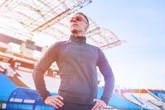 Stilig idrotts- man som poserar på det rinnande spåret av stadion arkivfoto