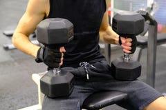 Stilig idrotts- man som utbildar hans skuldror med hantlar som sitter på en bänk i idrottshallen fotografering för bildbyråer