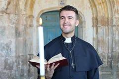 Stilig katolsk präst som ler i kyrka royaltyfri fotografi
