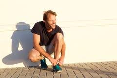 Stilig konditionman som ler och binder skosnöret fotografering för bildbyråer