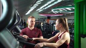 Stilig lagledare som talar till den unga sportiga kvinnan i idrottshallen arkivfilmer