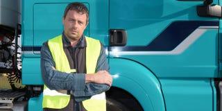 Stilig lastbilsförare för man med lastbilen bakom arkivbild