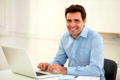 Stilig latinsk affärsman som ler på dig arkivbild