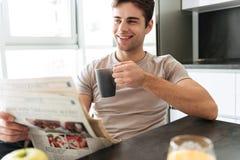 Stilig le man med den läs- tidningen för kopp te i kök Royaltyfria Bilder