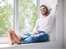 Stilig le man som kopplar av på fönsterfönsterbräda royaltyfria foton