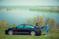 Stilig le man som sitter i hans bil med öppnade dörrar fotografering för bildbyråer