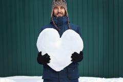 Stilig le skäggig hipsterman i vinterkläder som rymmer en stor hjärta gjord av snö, på grön väggbakgrund for för förälskelse för  royaltyfri fotografi