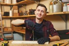 Stilig le ung man som arbetar i snickeriseminarium på trätabellstället med stycket av trä royaltyfri fotografi