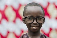 Stilig liten afrikansk pojke som utomhus på ler med stora svarta exponeringsglas royaltyfri foto