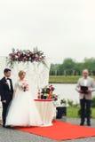Stilig lycklig brudgum och härlig blond brud i vit klänning a Royaltyfri Bild