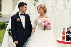 Stilig lycklig brudgum och härlig blond brud i vit klänning a Royaltyfria Bilder