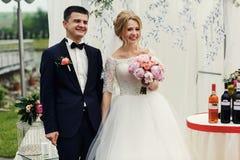 Stilig lycklig brudgum och härlig blond brud i vit klänning a Arkivbild