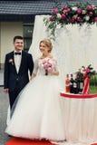 Stilig lycklig brudgum och härlig blond brud i vit klänning a Royaltyfria Foton