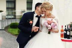 Stilig lycklig brudgum och härlig blond brud i vit klänning a Arkivfoto