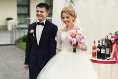 Stilig lycklig brudgum och härlig blond brud i vit klänning a Royaltyfri Fotografi