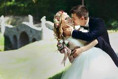 Stilig lycklig brudgum och lebrud i elegant vit klänning in Arkivfoto