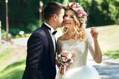 Stilig lycklig brudgum och lebrud i elegant vit klänning in Arkivbilder