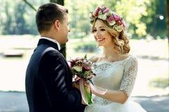 Stilig lycklig brudgum och lebrud i elegant vit klänning in Royaltyfri Foto