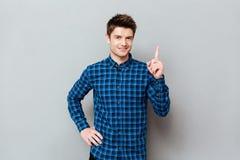 Stilig lycklig ung man som står över den gråa väggen och att peka Royaltyfria Bilder
