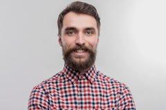Stilig mörker-haired skäggig man som bär den ljusa kvadrerade skjortan arkivbild