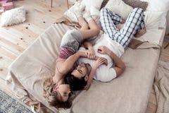 Stilig mörker-haired ung man i en vit skjorta och hans gulliga blonda sova för fru royaltyfri foto