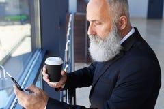 Stilig manålder av hållande kopp kaffe 50-60 och att surfa i p Arkivfoton