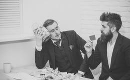 stilig man för framsida Den trötta mannen som håll skorrar mycket av kassa, kollega, rymmer kreditkorten Affärspartners affärsmän arkivbild