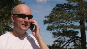 Stilig man för stående som talar vid mobiltelefonen i grön skog på sommardagen lager videofilmer