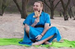 Stilig man för Tricki transsexuell som sitter på sand i den blåa kimonot som väljer tänder med skeppmodellen arkivbild