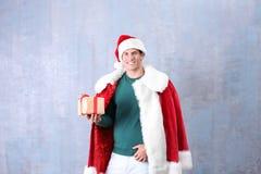 Stilig man i ask för gåva för Santa Claus dräkt hållande Royaltyfria Bilder