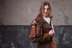 Stilig man i den bruna kappan, ångapunkrockstil Retro manstående över grungebakgrund Fotografering för Bildbyråer