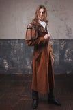 Stilig man i den bruna kappan, ångapunkrockstil Retro manstående över grungebakgrund Royaltyfri Foto