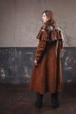 Stilig man i den bruna kappan, ångapunkrockstil Retro manstående över grungebakgrund Arkivfoton