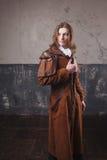 Stilig man i den bruna kappan, ångapunkrockstil Retro manstående över grungebakgrund Royaltyfri Fotografi
