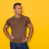 Stilig man i den bruna T-tröja som bort ser royaltyfri foto