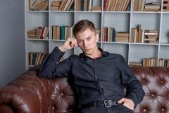 Stilig man i den svarta skjortan som sitter p? soffan vid bokhyllor f?r begreppsframsida f?r sk?nhet bl? ljus kvinna f?r makeup f arkivfoto
