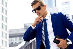 Stilig man i en blå dräkt mot en stadsbakgrund på en solig dag Arkivfoton