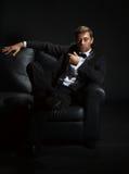 Stilig man i en smoking på soffan arkivbild