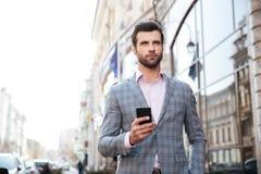 Stilig man i ett omslag som går och rymmer mobiltelefonen fotografering för bildbyråer