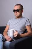 Stilig man i exponeringsglas som 3d sitter på soffan och hållande ögonen på filmwi Royaltyfria Bilder